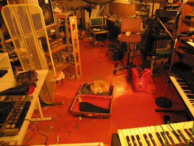 An orange tabby lies in a suitcase in the middle of a work room filled with keyboards, electronics, speakers, synthesizers
