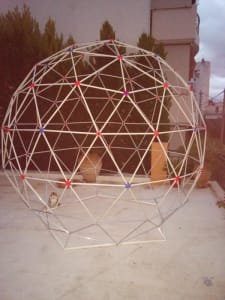 calico cat sitting outside underneath a white collapsible geodesic dome