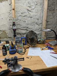 A tabby crouches on a workstation, in among a soldering iron, clamp, magnifier, tweezers, Winnie the Pooh glass, wires, and pens