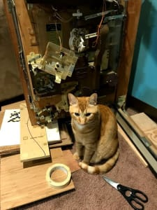 An orange cat sits in front of an incomplete electronics project. There are various components dangling from wires. On the floor, in front of the cat, there is a pair of scissors and a roll of tape.