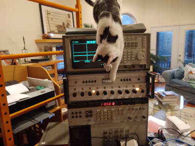 A white cat with dark grey spots hangs over a tower of electronic equipment. The cat is pawing at the monitor of an oscilloscope and control knobs below