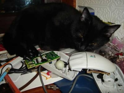 Black cat sleeps atop a pile of electronics, including a computer mouse.