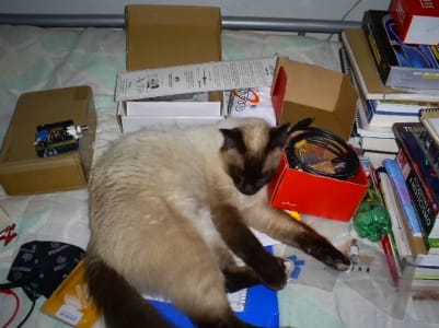 A siamese cat sleeps on top of a spiral binder surrounded by books wires and boxes.