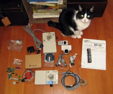 A black and white cat stares directly into the camera. Next to the cat are various electronics laid out uniformly on the wooden floor.