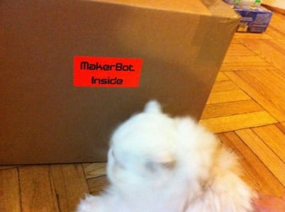 "A white long haired cat sits next to a cardboard box that says ""maker bot inside""."