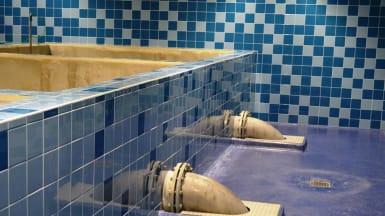 Bild på en blåkakelfärgad vattenbassäng, med rör som utgår från väggen och dyker i golvet.