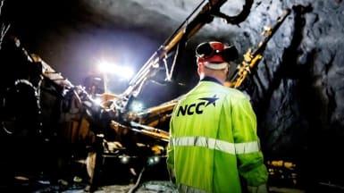 En yrkesarbetare och borrmaskiner uppehåller sig i en upplyst tunnel.