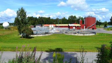 Bland nyklippt gräs och skog står vattenbassänger och rödmålade avloppsreningsanläggningar.