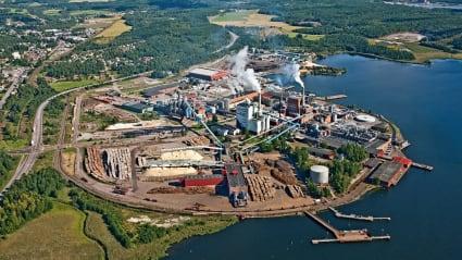 Flygfoto över Gruvöns pappersbruk i Grums, stor industri med skog åt vänster, vatten åt höger.
