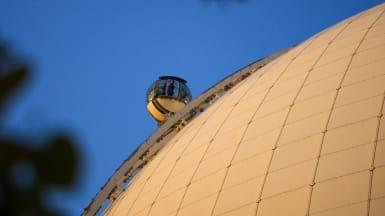 Bild på Globens yttre vita fasad, med SkyView-hissen som åker på sin räls.