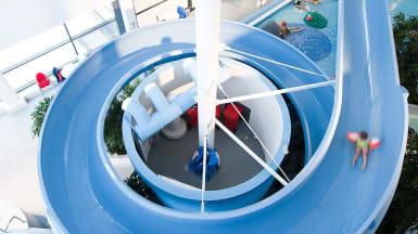 En blå, cirkulär vattenrutschkana skjutsar ner ett barn mot poolen.