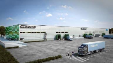 Bild på logistiklokalen Hälsobrunnen, en del av Brunna logistikpark. Rektangulär byggnad med vit fasad på bredsidan och gröna mönster på kortsidan.