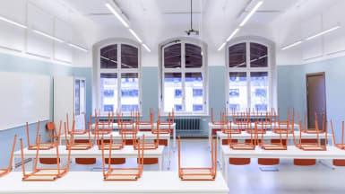 Bild på en nyrenoverad skolmatsal med blåvita väggar. På borden står uppställda orangea stolar.