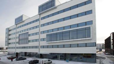 På en vit fasad med utbuktande fönsterelement.