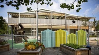 Bild på en skola gjord med NCC passivhus, med lekplatsen bakom omväxlande stängsel och färgglada staket.