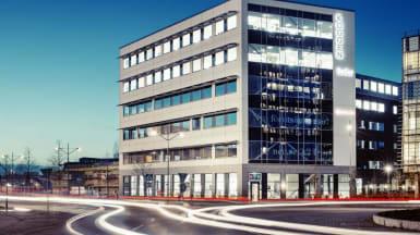 Bild på kontorshuset Koggen 2 med grå fasad och små fönsterrader vid varje våning.