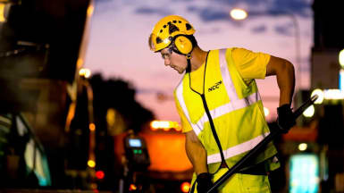 Picture of a worker laying asphalt in the dusk.