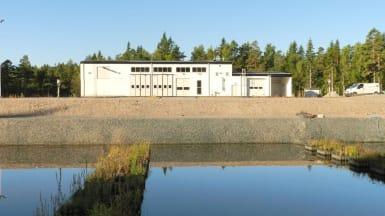 I förgrunden en vattenreservoar, ovanför den ligger avloppsreningsverket med vit fasad och industriell stil.