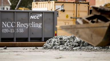Bild på två containrar, stenkross och en grävskopa som håller metallskrot. På den ena containern står det