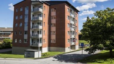 Bild på ett hus med röd tegelfasad och balkonger som ligger