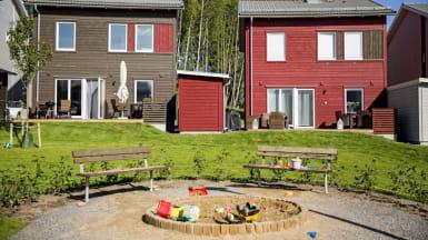 I förgrunden två parkbänkar, bortom parkbänkarna finns gräsmatta och bruna samt röda småhus med altan.
