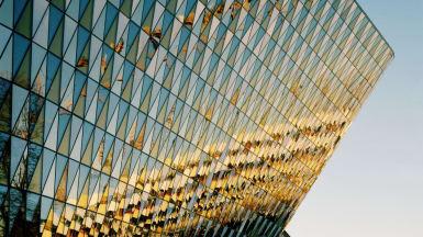 Detaljbild på Nya Aulan, Karolinska institutet. Triangulära glasformer mönstrar väggen. En annan byggnad reflekterar sig på väggen.
