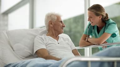 Picture of an elderly man socializing with a hospital worker.