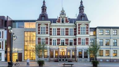 Rådhuset i Kristianstad. En ståtlig byggnad med rödvit fasad, och två torn som sticker upp på vardera sida.