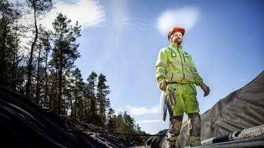 En arbetare står vid en utgrävd vall och blickar bortåt mot kamerans håll. Bland honom finns nyinstallerade likströmskablar.