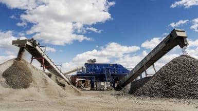 Två högar med grus framför ett stort maskineri på en av NCC:s täckter för material