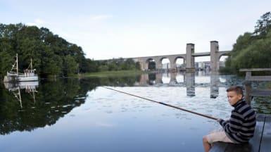 En pojke sitter vid en brygga och fiskar medan Östra Årstabron syns i bakgrunden.