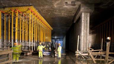 Inuti Malmös Citytunnel, under uppbyggnad. Byggarbetare strövar omkring, och stödfundament för betong samt byggplank syns.