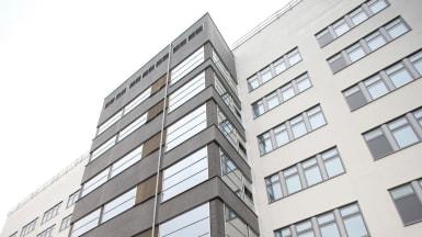 Vy nedanifrån på Tehuset, Borås med omväxlande vit fasad och utbuktande grå fasad.