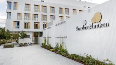 Bild på en vit stödvägg till Skandionkliniken, med dess logga i bildens högra hörn. På marken finns cykelparkering och trädplantering.