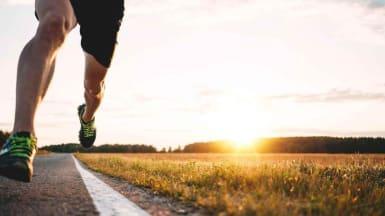 En person springer på asfalterad väg i solnedgång.