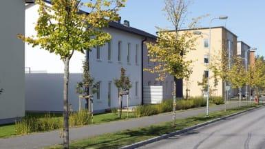 Bild på rad- och flerbostadshus i olika färger, med en trottoar som går vid sidan om.