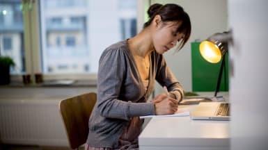 En person sitter vid skrivbordet och skriver i sitt anteckningsblock.