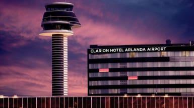 Under en vacker kvällshimmel syns Arlandas kontrolltorn och det nya Clarion Hotel med svart fasad och fönsterremsor.