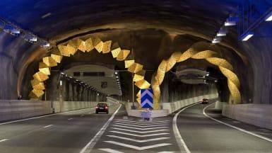 Inuti Södra Länken, Stockholm. Sprutbetongtäckta tunnelväggar lyses upp i blått, med dekoration där avfarten svänger från huvudvägen.