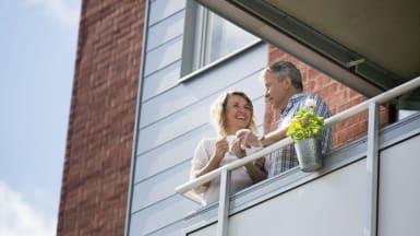 Två personer njuter på en balkong. Den ena håller i en kopp.