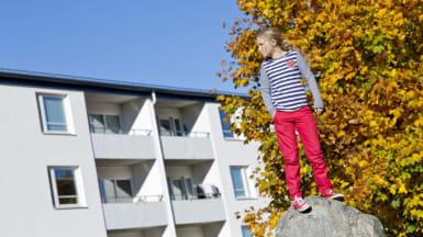 En flicka står på en sten, med ett vitt radhus åt vänster bakgrund och ett höstfärgat träd åt höger bakgrund.