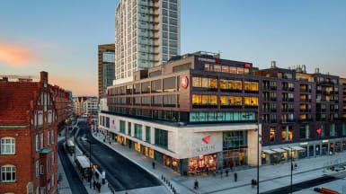 Överblick över Malmös stadsdel Triangeln, med gallerian i mitten som ändrar stil från vit stenfasad till brun fasad mellan andra och tredje våningen.