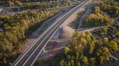 Bild på nya Riksväg 50, med en nyanlagd väg som skär genom skog och förbi byggnation.