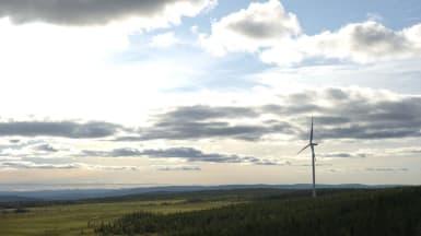 Ett enstaka vindkraftverk virvlar på ett utbrett landskap.