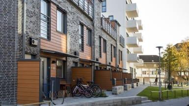 Kvarteret Trevnaden, moderna rad- och flerbostadshus med omväxlande svart tegelstensfasad och vit betongfasad.