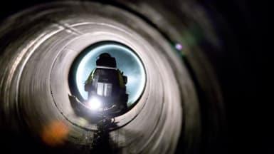 Bild på en vattenlednings tunnel, med en maskinist synlig i slutet av rörtunneln.