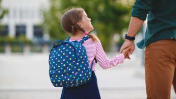 Bild på en liten flicka som håller i en vuxen.