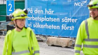 I förgrunden två NCC-merdarbetare, i bakgrunden ett stängsel med skyltar.