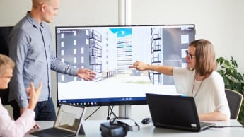 Tre medarbetare diskuterar en digital skiss.