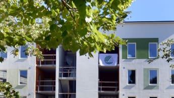 Bild på ett lägenhetshus där en textil med Svanenmärket fladdrar längs med en balkong.